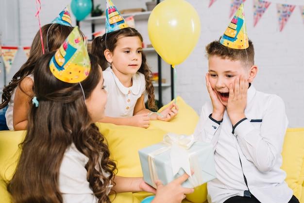 Dziewczyna podając opakowane pudełko do zaskoczony urodziny chłopca w partii