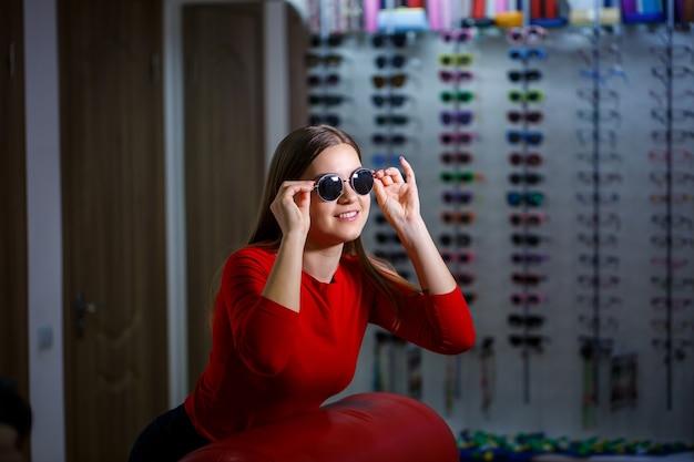 Dziewczyna podnosi okulary przeciwsłoneczne. sklep z okularami. korekcja wzroku. stojak na okulary