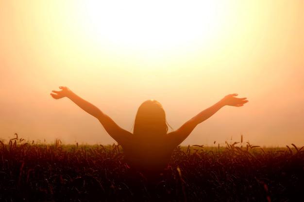 Dziewczyna podnosi ręce do nieba i czuje wolność.