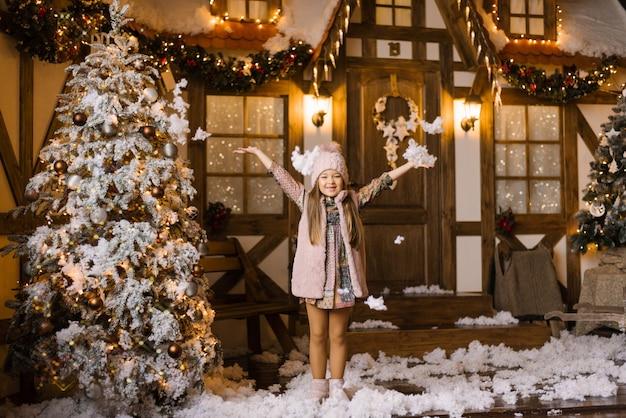 Dziewczyna podnosi ręce i posypuje śnieg na tle świątecznego domu i choinki pokrytej sztucznym śniegiem