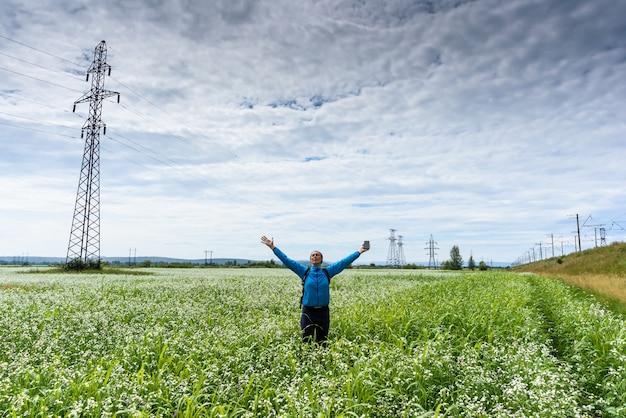 Dziewczyna podnosi ręce na piękną zieloną łąkę.