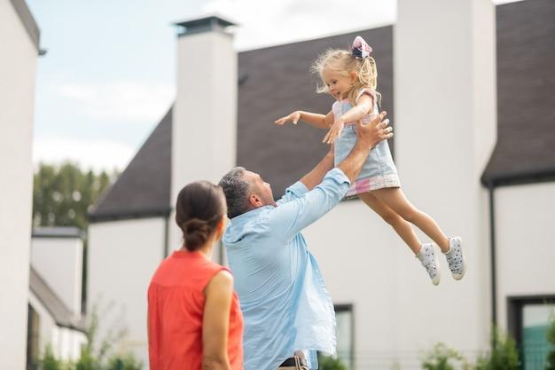Dziewczyna podnoszenia ojca. urocza urocza, atrakcyjna córka czuje się niesamowicie, podczas gdy ojciec ją podnosi