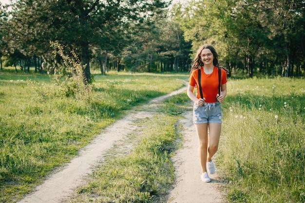 Dziewczyna podróżnik na wiejskiej drodze.