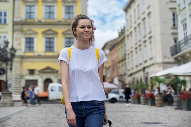 Dziewczyna podróżnik spaceru z plecakiem i żółtą walizką wzdłuż ulicy miasta turystycznego