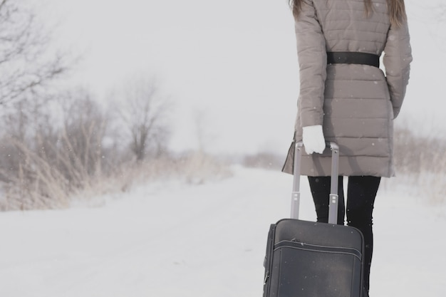Dziewczyna podróżuje z walizką. zimowa droga i młoda dziewczyna.