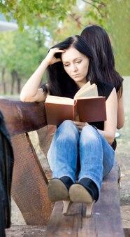Dziewczyna pogrążona w czytaniu książki, relaksując się na rustykalnej drewnianej ławce ogrodowej