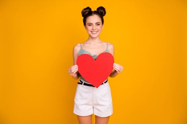 Dziewczyna pokaż duże czerwone serce karty papieru na białym tle nad żółtym kolorem