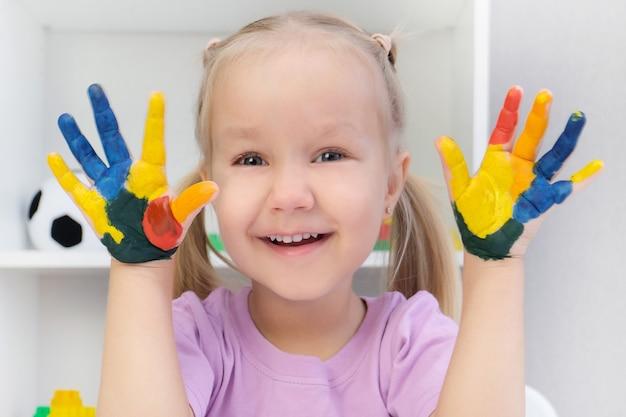 Dziewczyna pokazując malowane ręce. ręce pomalowane kolorowymi farbami. koncepcja edukacji, szkoły, sztuki i malarstwa