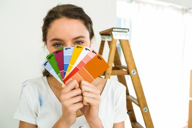 Dziewczyna pokazująca próbki kolorów do aparatu