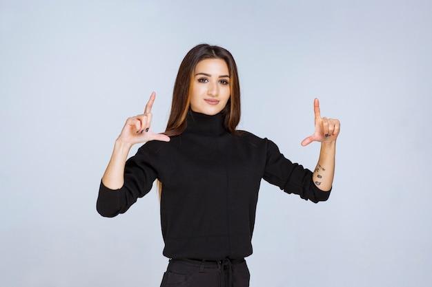 Dziewczyna pokazująca rozmiar obiektu rękami. zdjęcie wysokiej jakości