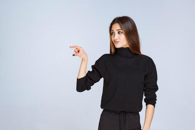 Dziewczyna pokazująca szacunkowe wymiary obiektu. zdjęcie wysokiej jakości