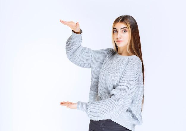 Dziewczyna pokazująca wymiary obiektu.