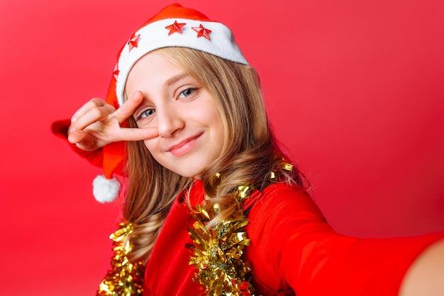 Dziewczyna pokazuje gest powitalny i bierze selfie w czapce świętego mikołaja
