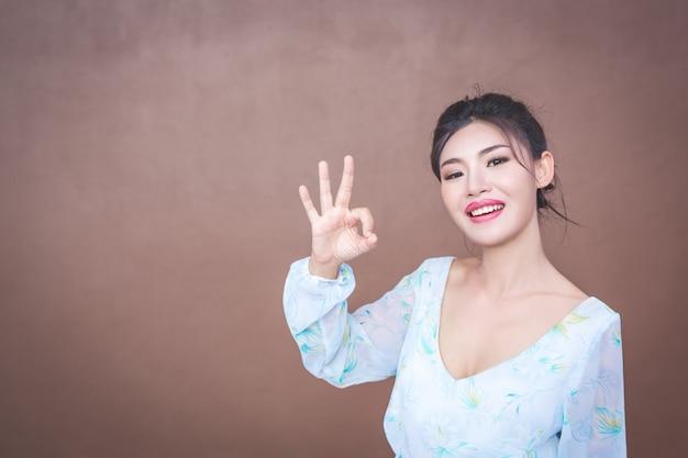 Dziewczyna pokazuje gesty dłoni i emocje twarzy.