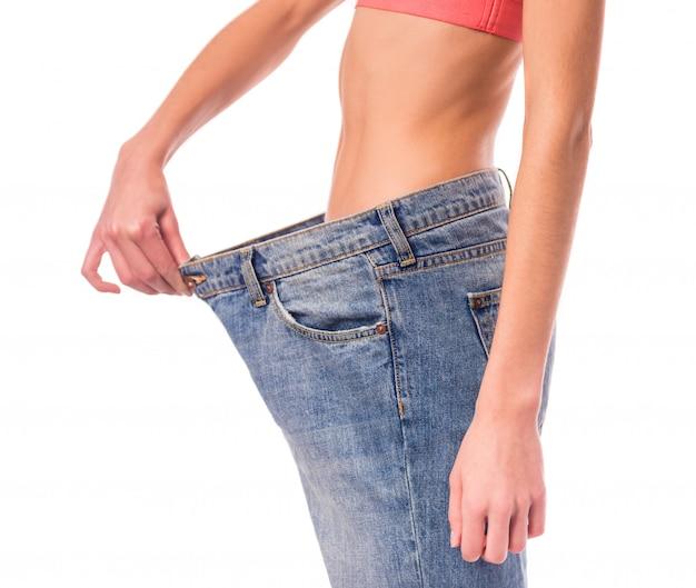 Dziewczyna pokazuje ich utratę wagi, na przykład dżinsy.