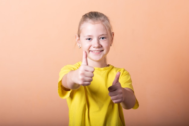Dziewczyna pokazuje kciuk w górę, na jasnopomarańczowym tle. w dowolnym celu.