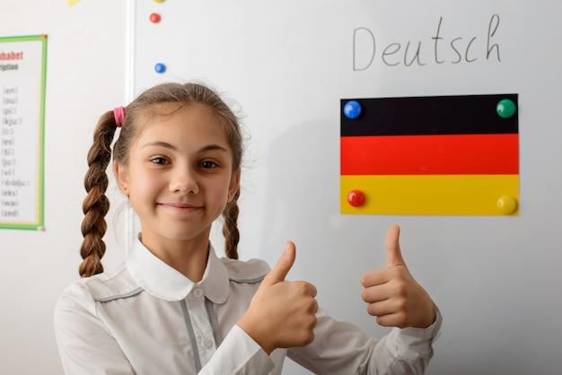 Dziewczyna pokazuje kciuki w pobliżu flagi niemiec
