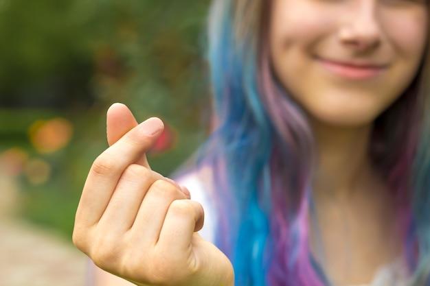 Dziewczyna pokazuje koreański symbol miłości serca z palców.