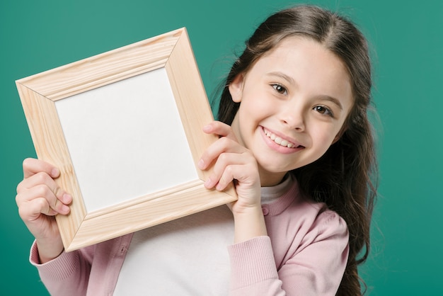 Dziewczyna pokazuje obrazek ramę w studiu
