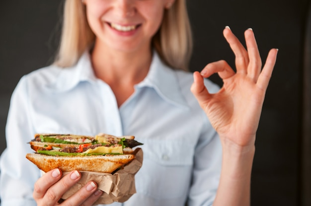 Dziewczyna pokazuje ok trzyma kanapkę