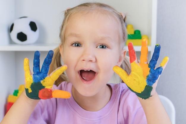 Dziewczyna pokazuje pomalowane ręce. ręce pomalowane kolorowymi farbami.