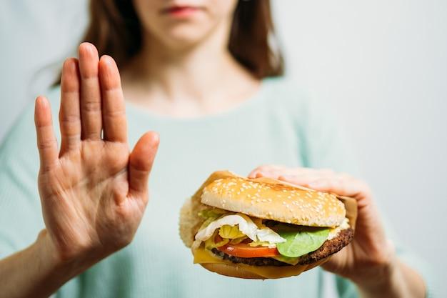 Dziewczyna pokazuje stop burgera. pojęcie zdrowego stylu życia.