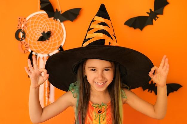 Dziewczyna pokazuje znak ok, robiąc dobry gest palcami, podczas gdy pomarańczowe tło z nietoperzami