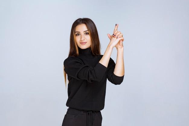 Dziewczyna pokazuje znak pistolet w dłoni. zdjęcie wysokiej jakości