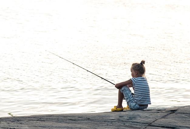 Dziewczyna połów przy jeziorem w wakacje