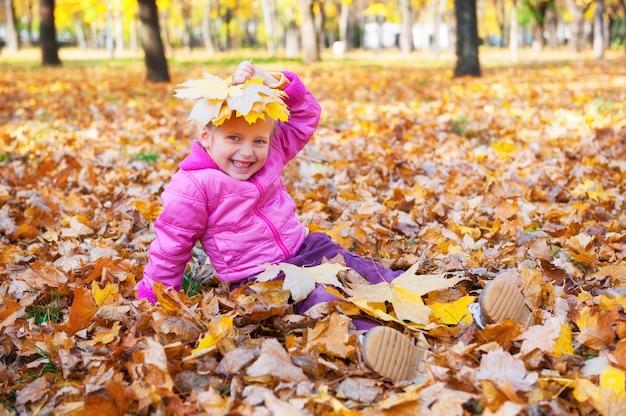 Dziewczyna położyła liście na głowie w jesienny park