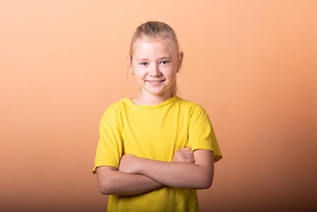 Dziewczyna położyła ręce na biodrach, na jasnopomarańczowym tle. w dowolnym celu.