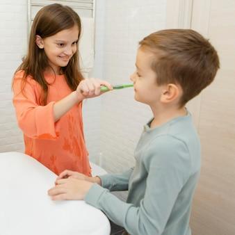 Dziewczyna pomaga bratu umyć zęby