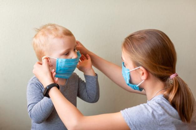 Dziewczyna pomaga jej braciszkowi założyć maskę medyczną