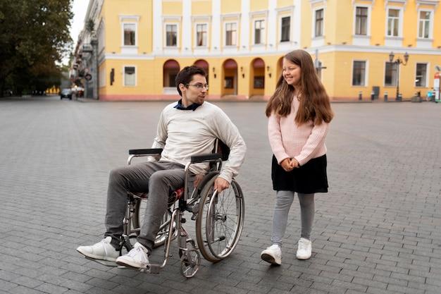 Dziewczyna pomaga niepełnosprawnemu mężczyźnie podróżującemu po mieście