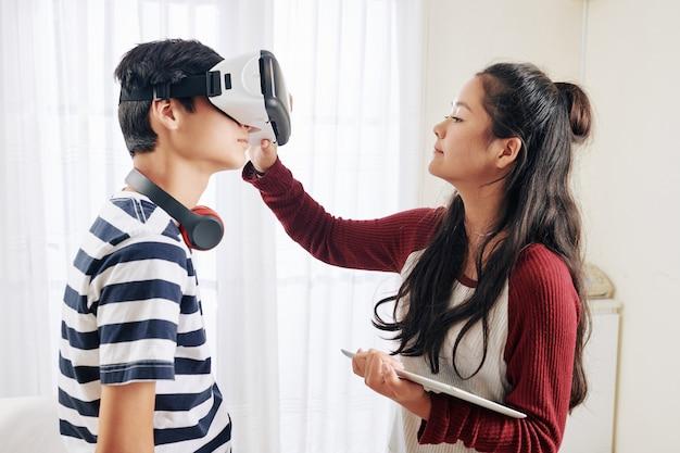 Dziewczyna pomaga nosić okulary vr