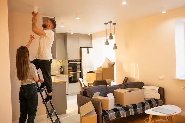 Dziewczyna pomaga swojemu chłopakowi wkręcać żarówkę w domu. europejska para. pudełka kartonowe z rzeczami. koncepcja przeprowadzki do nowego mieszkania. idea młodej rodziny. wnętrze apartamentu typu studio. słoneczny dzień