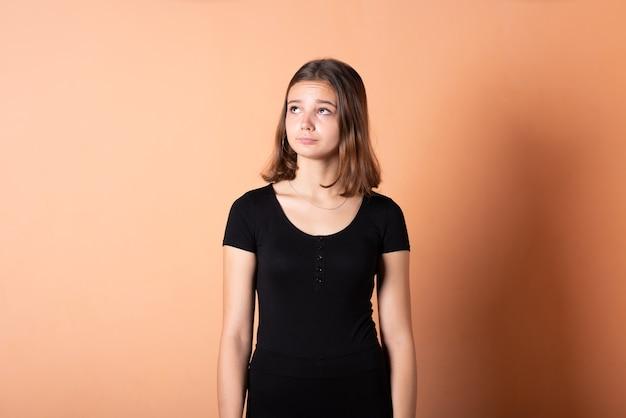 Dziewczyna pomyślała i spojrzała w górę na jasnopomarańczowym tle. w dowolnym celu.