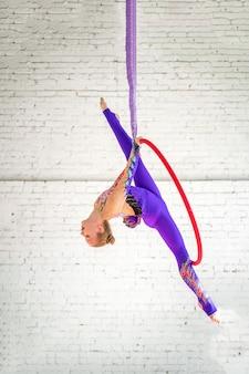 Dziewczyna powietrzna gimnastyczka na okręgu robi akrobatycznym elementom