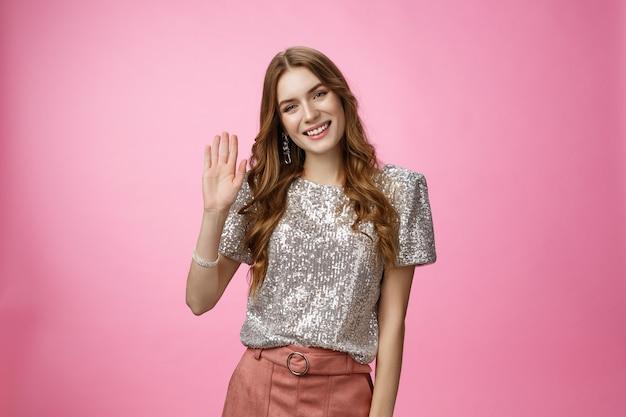 Dziewczyna poznaje ludzi imprezuje podnieście machając dłonią uśmiechając się przywitaj się pokaż cześć gest powitania wigilię...