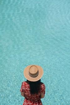 Dziewczyna pozująca przy basenie w modnym stroju kąpielowym z basenem odbija się w tle / letniej aktywności