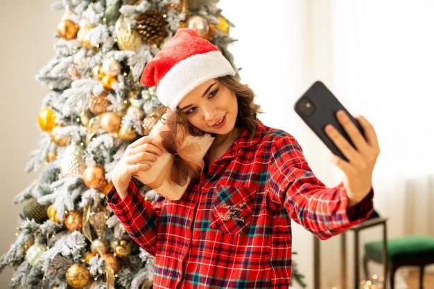 Dziewczyna pozuje i robi selfie w pobliżu choinki. kobieta gratuluje krewnemu przez telefon. trzyma prezent w ręku i uśmiecha się.