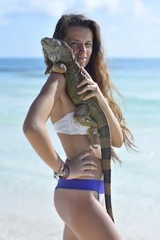Dziewczyna pozuje na karaibskiej plaży z iguana