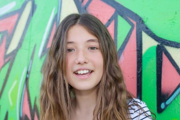 Dziewczyna pozuje obok graffiti