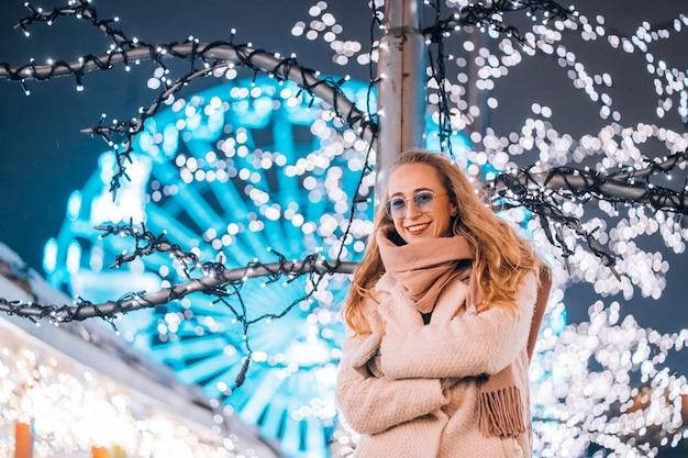 Dziewczyna pozuje przeciw tłu dekorujący drzewa