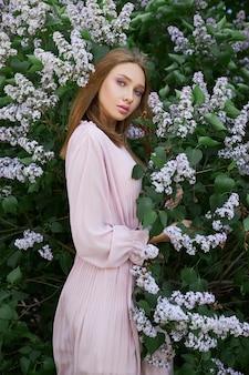 Dziewczyna pozuje w bzu na wiosnę. romantyczny portret dziecka w kwiatach w świetle słonecznym