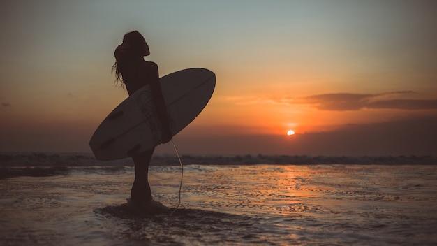 Dziewczyna pozuje z deską o zachodzie słońca
