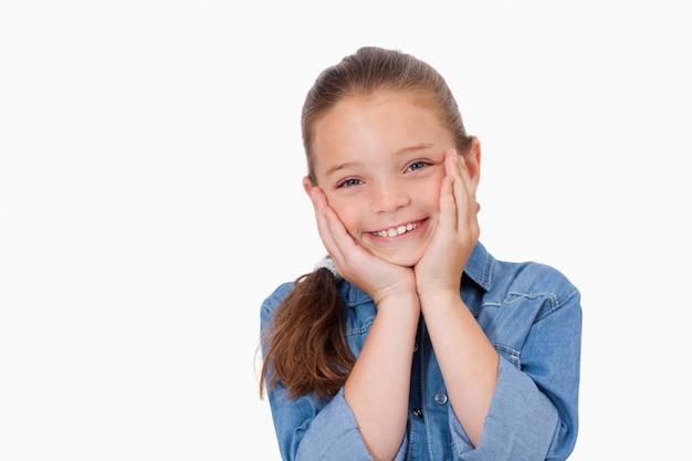 Dziewczyna pozuje z rękami pod jej podbródkiem