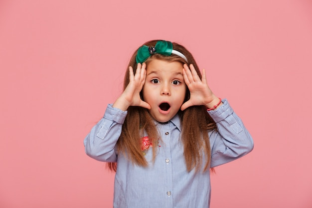 Dziewczyna pozuje z szeroko otwartymi oczami i ustami, będąc emocjonalnym i zaskoczonym
