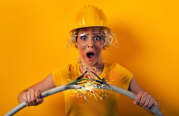 Dziewczyna pracownika z hełmem ochronnym, trzymając kabel elektryczny