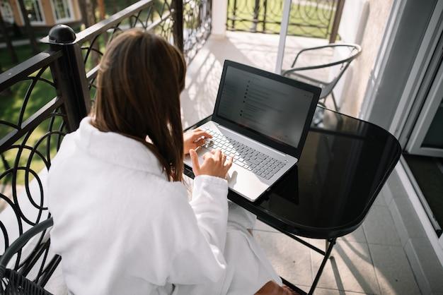 Dziewczyna pracuje na balkonie ze swoim laptopem w białej szacie